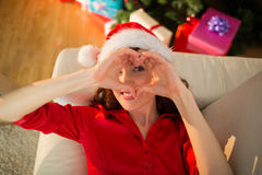 Smiling redhead doing heart sign at christmas Royalty Free Stock Photography