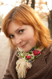 Smiling redhead girl in autumn park Royalty Free Stock Photos