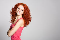 Smiling redhead girl on a background of gray wall Royalty Free Stock Image