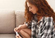 Smiling girl reading the results of her pregnancy test. Smiling redhead girl checking her recent pregnancy test, sitting on beige couch at home, copy space royalty free stock image