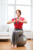 Smiling redhead girl exercising with fitness ball Stock Photos