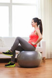 Smiling redhead girl exercising with fitness ball Stock Image