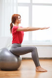 Smiling redhead girl exercising with fitness ball Royalty Free Stock Photos