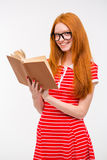 Smiling redhead girl in glasses reading a book Royalty Free Stock Photography