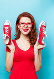 Smiling redhead girl with gumshoes Royalty Free Stock Image