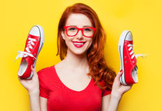 Smiling redhead girl with gumshoes. On yellow background Stock Image