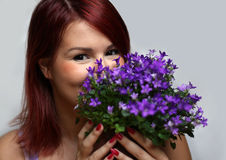 Smiling redhead girl holding pot with flowers Stock Photos