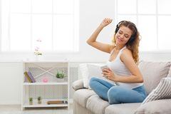 Happy young woman in headphones on beige couch. Smiling redhead girl listening to music online on smartphone in headphones, sitting on beige couch at home, copy Stock Photo