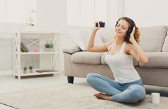 Happy young woman in headphones on floor stock photos