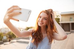 Smiling redhead girl with long hair taking a selfie. While standing over city street background royalty free stock photos