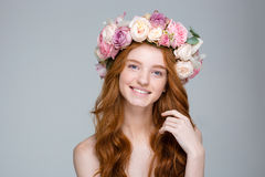 Smiling redhead girl with long hair in wreath of roses Royalty Free Stock Photo