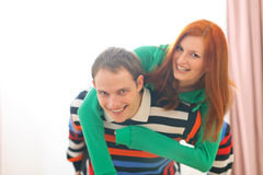 Smiling redhead girl piggybacking boyfriend Royalty Free Stock Image