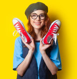Smiling redhead girl with red gumshoes Stock Images