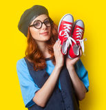 Smiling redhead girl with red gumshoes Royalty Free Stock Photography