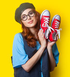 Smiling redhead girl with red gumshoes Royalty Free Stock Photo