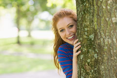 Smiling redhead hiding behind a tree. On college campus Stock Photos