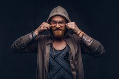 Smiling redhead hipster with full beard and glasses dressed in hoodie and t-shirt poses in a studio. Isolated on a dark. Smiling redhead hipster with full beard stock photo