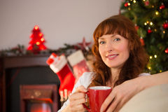 Smiling redhead holding a mug of hot drink at christmas Stock Photo