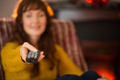 Smiling redhead holding remote control at christmas Stock Photography