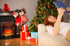 Smiling redhead lying on the couch using tablet Royalty Free Stock Images