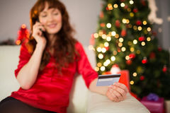 Smiling redhead phoning and holding credit card Stock Photo