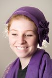 Smiling redhead in purple hat biting lip Royalty Free Stock Photo