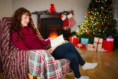 Smiling redhead reading on the armchair at christmas Royalty Free Stock Image