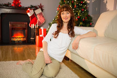 Smiling redhead sitting on carpet leaning against couch Royalty Free Stock Photography