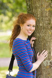 Smiling redhead student leaning on tree looking at camera Royalty Free Stock Photo