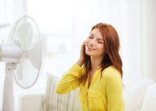 Smiling redhead teenage girl with big fan at home Royalty Free Stock Photo