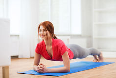 Smiling redhead teenage girl doing plank at home Stock Photography