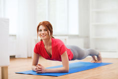Smiling redhead teenage girl doing plank at home Royalty Free Stock Photo