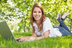 Smiling redhead using laptop in the park Royalty Free Stock Images