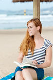 Smiling Redhead Woman With Book On Beach Stock Images