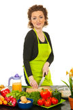 Smiling redhead woman cutting green onion Stock Photo