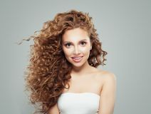 Smiling redhead woman with long healthy curly hair and clear skin. Cute girl on gray background stock image