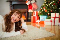 Smiling redhead woman lying on floor at christmas Royalty Free Stock Photography