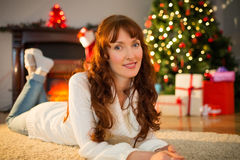 Smiling redhead woman lying on floor at christmas Royalty Free Stock Images