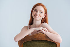 Smiling redhead woman sitting on the chair Stock Photography