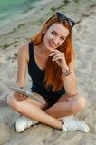 Smiling redhead woman sitting on sand. Smiling redhead woman sitting on sand and holding laptop Royalty Free Stock Image