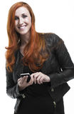 Smiling redhead woman using a mobile phone. Smiling attractive young redhead woman in a stylish black outfit standing using a mobile phone and looking at the Royalty Free Stock Image