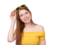Smiling redheaded female in yellow top and sunglasses Royalty Free Stock Photo