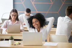 Happy student or employee enjoying break at workplace feeling re. Smiling relaxed african american women resting after computer work in office hands behind head stock photo
