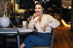 Smiling relaxed Asian businesswoman sitting in cafe stock photos