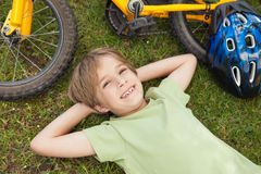Smiling relaxed boy with bicycle at park. High angle portrait of a smiling relaxed boy with bicycle at the park Royalty Free Stock Photo