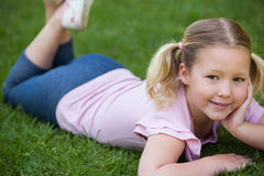 Smiling relaxed girl lying on grass at park Stock Images