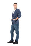 Smiling relaxed man in jeans and denim shirt with hands in pockets. Full body length portrait isolated over white background Royalty Free Stock Image