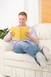 Smiling relaxed man reading book. Stock Image