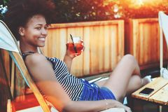Afro girl with drink in street bar Royalty Free Stock Image