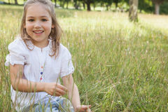 Smiling relaxed young girl sitting in field Royalty Free Stock Image